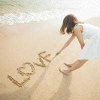 砂浜に文字を書く女性